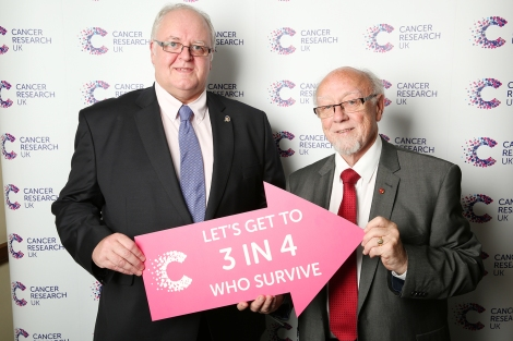 Jim with Cancer Research UK Campaigns Ambassador David Collins hold an arrow emblazoned with the words 'LET'S GET TO 3 IN 4 WHO SURVIVE'. This represents Cancer Research UK's ambition to boost the number of people surviving cancer from two in four today, moving to three in four within the next 20 years.